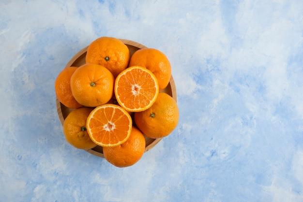 Vista dall'alto. pila di mandarini clementine sul piatto di legno sulla superficie blu
