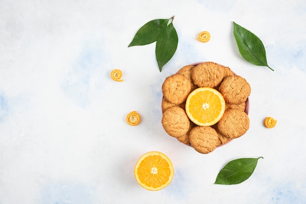 Top view of pile of cookies with half cut orange and leaves over white table. high quality illustration