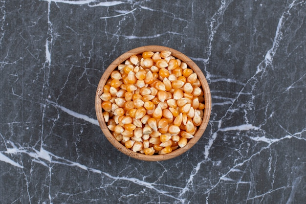Top view. pile of corn seeds in wooden bowl.