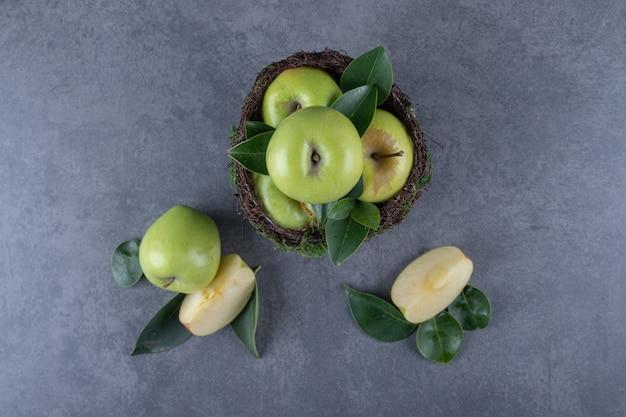 Vista dall'alto . pila di mele fresche e fette su sfondo grigio.