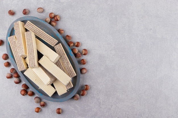 Top view of pile of homemade wafers on wooden tray over grey surface with walnuts