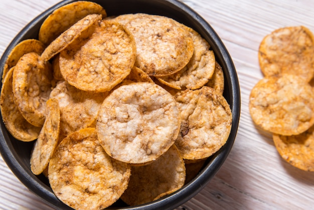 Top view pile of organic, crispy, baked, whole grain rice chips with spices. gluten free healthy snack. black ceramic bowl on wooden table