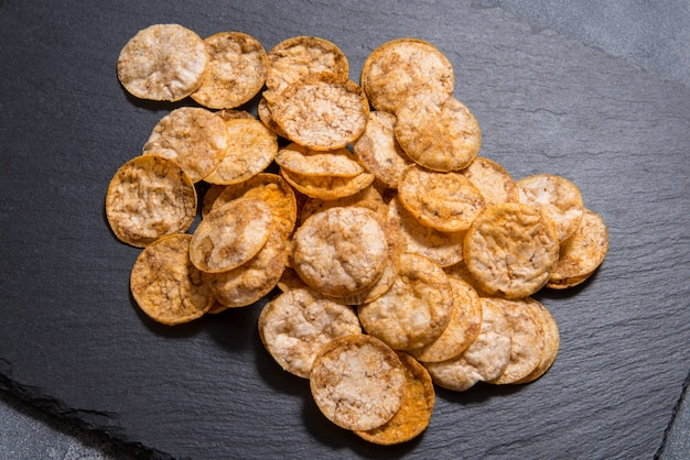 Top view pile of organic, crispy, baked, whole grain rice chips with spices. gluten free healthy snack. on black sliced stone surface