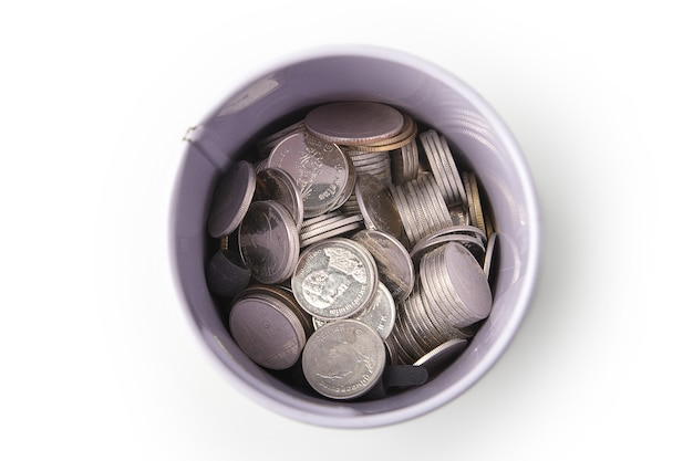 Top view of pile of thai coins in a can bank isolated on a white background, saving money.