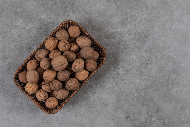 Top view of pile of walnuts in basket over grey table.