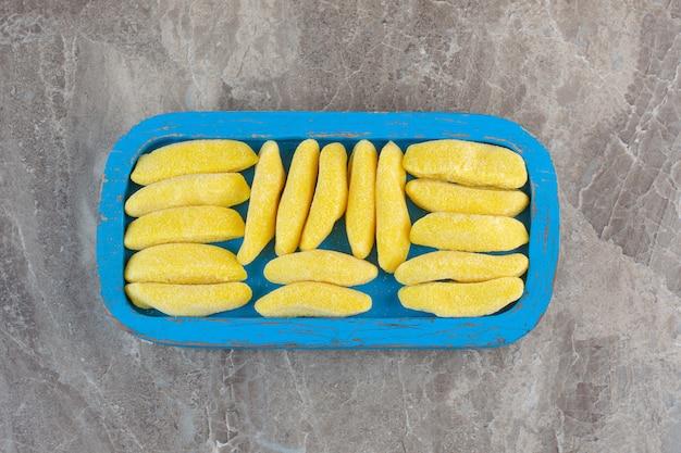 Vista dall'alto del mucchio di caramelle gialle sul piatto di legno blu.