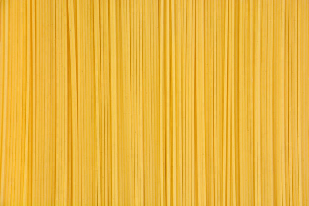 Top view pile of yellow raw spaghetti texture background
