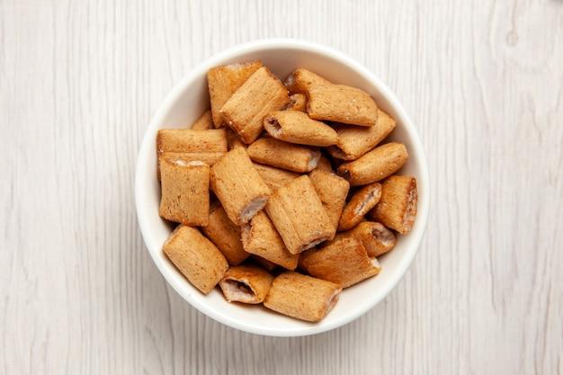 Вид сверху подушка, печенье, сладкое печенье внутри тарелки на белом столе