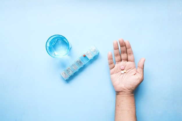 Top view of pills on palm of hand with pill box and glass on water on table