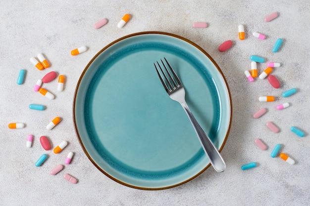 Pillole vista dall'alto e piatto con forchetta