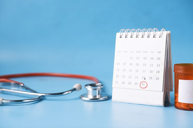Top view of pills and stethoscope on calendar