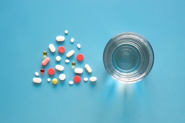 Top view of pills in triangle shape with glass of water