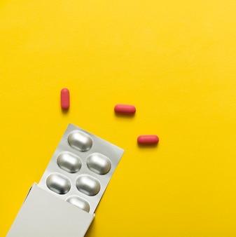 Vista dall'alto di pillole con pellicola e scatola
