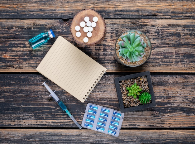 Top view pills on wood stub with cactus, notepad and needle on dark wooden background.