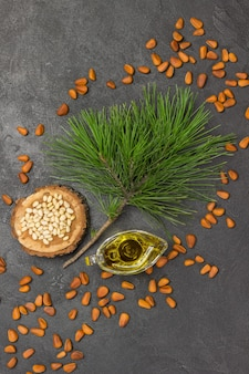 Top view pine nuts, oil, and cedar branch