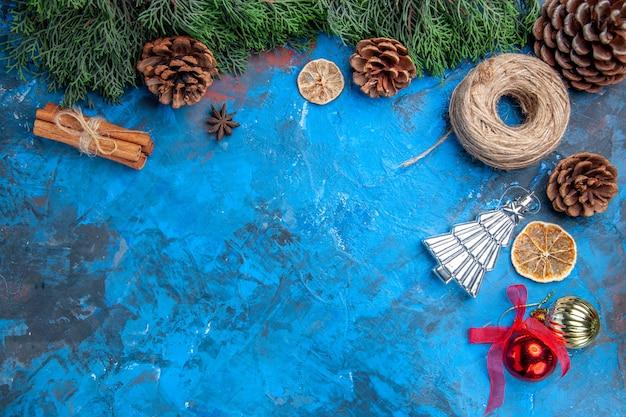 Vista dall'alto rami di pino filo di paglia bastoncini di cannella fette di limone essiccate albero di natale giocattoli su superficie blu-rossa