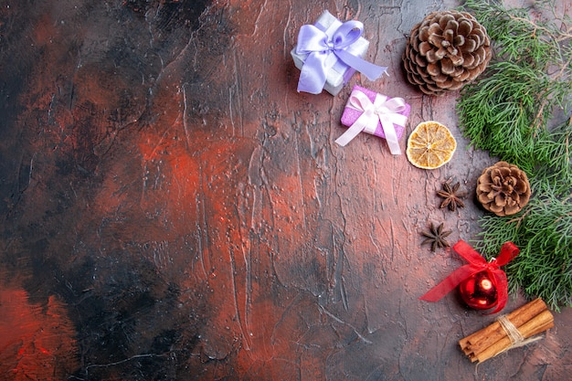 Вид сверху ветка сосны с шишками, анисом, корицей, рождественские детали на темно-красном фоне, бесплатное место, рождественское фото