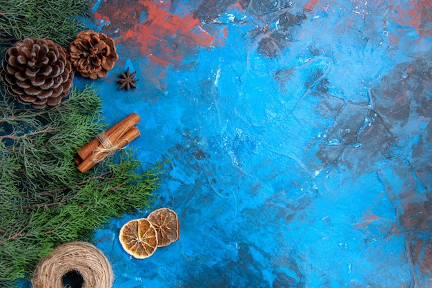 Top view pine tree branches cones straw thread cinnamon sticks anise seed dried lemon slices on blue-red background with free place