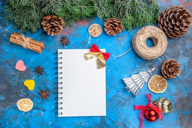 Вид сверху ветки сосны, шишки, соломенная нить, палочки корицы, семена аниса, елочные шары, конфеты в форме сердца, блокнот на сине-красном фоне