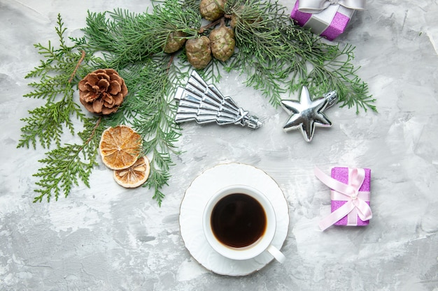 Top view pine tree branches cup of tea dried lemon slices pinecones small gifts on grey background