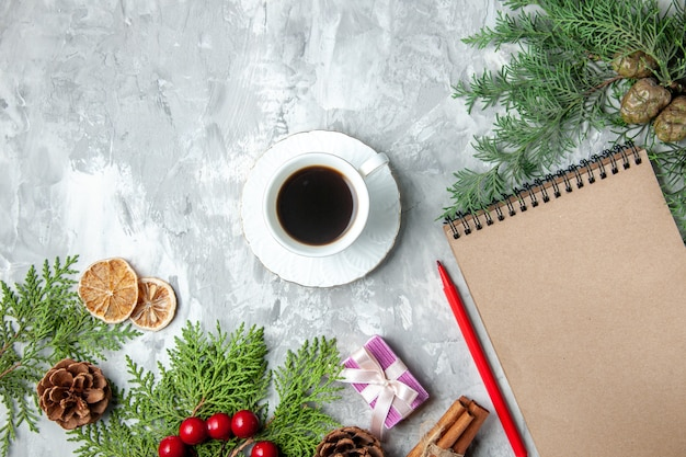 Top view pine tree branches cup of tea small gifts xmas tree toys notebook pencil on grey surface
