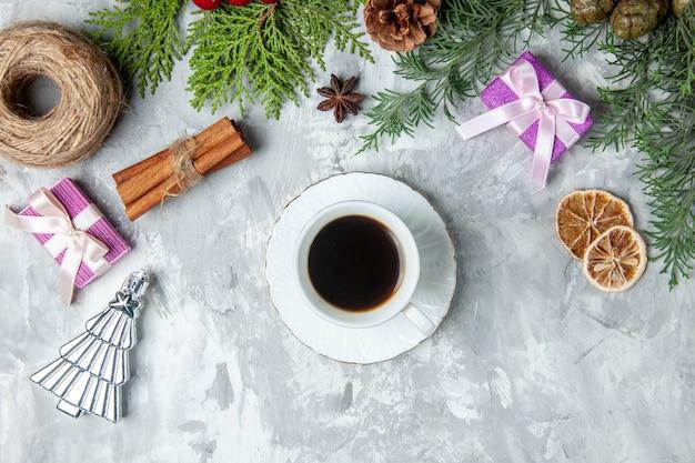 Vista dall'alto rami di pino tazza di tè filo di paglia bastoncini di cannella piccoli regali su superficie grigia