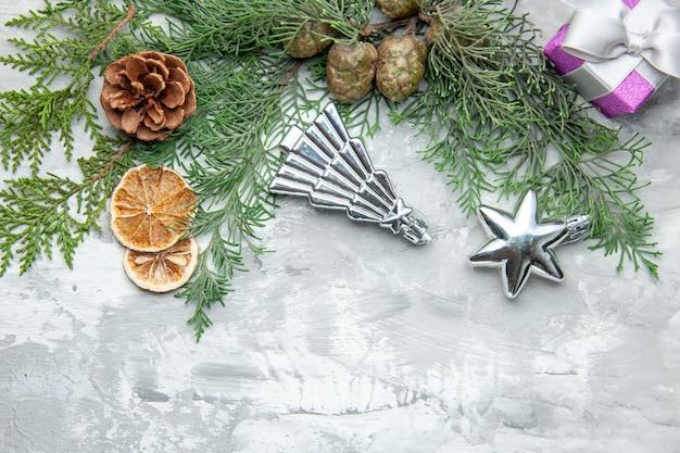 Vista dall'alto rami di pino fette di limone pigne piccolo regalo albero di natale giocattoli su sfondo grigio