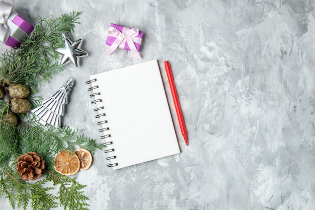 Top view pine tree branches notebook pencil lemon slices pinecones small gifts on grey background copy space
