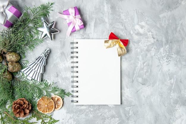 Vista dall'alto rami di pino notebook pigne piccoli regali su sfondo grigio spazio copia gray