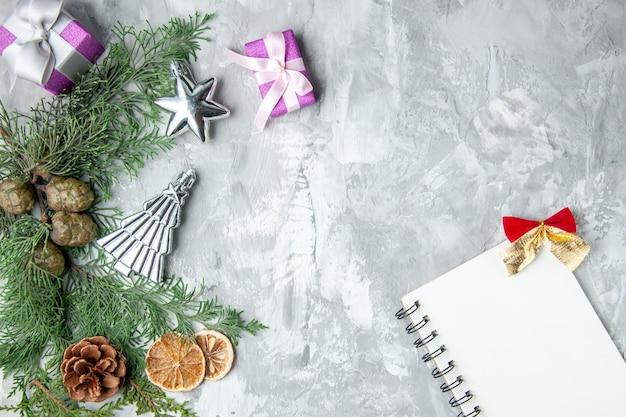 Вид сверху ветки сосны, ноутбук, шишки, маленькие подарки на серой поверхности