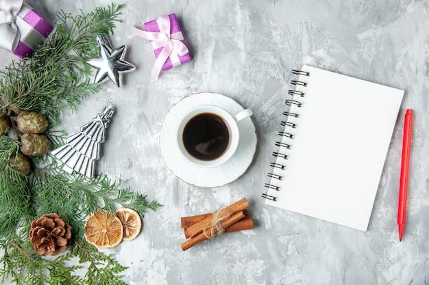 상위 뷰 소나무 나뭇가지 노트북 빨간색 연필 컵 차 계피 스틱 솔방울 회색 배경에 작은 선물