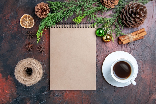 Top view pine tree branches and pinecones a notebook cup of tea anises cinnamon cup of tea straw thread on dark red surface