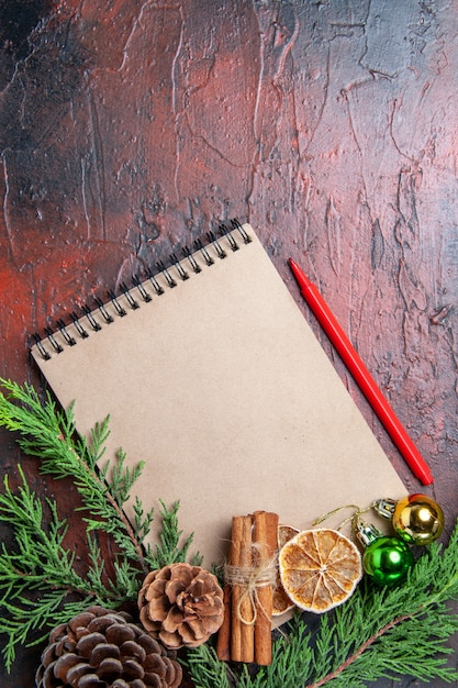 Top view pine tree branches and pinecones on a notebook red pen dried lemon slices cinnamon on dark red surface free space