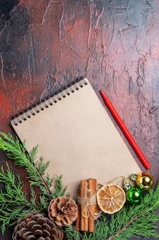Vista dall'alto rami di un albero di pino e pigne nelle quali su un taccuino penna rossa essiccato fette di limone cannella sulla superficie rosso scuro spazio libero