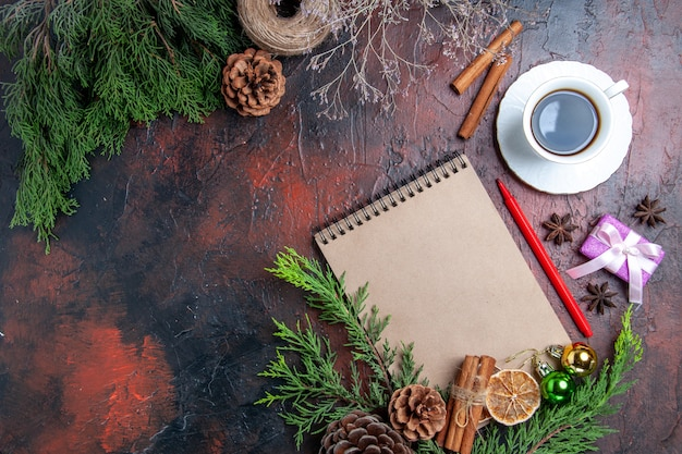 Top view pine tree branches and pinecones a notebook red pen dried lemon slices straw thread cup of tea star anises on dark red surface with free place