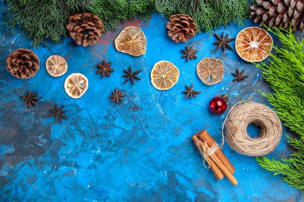 Vista dall'alto rami di pino pigne filo di paglia bastoncini di cannella fette di limone essiccate semi di anice su superficie blu-rossa