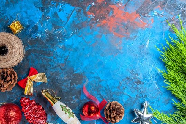 Vista dall'alto rami di pino pigne filo di paglia natale ornamenti appesi su superficie blu-rosso