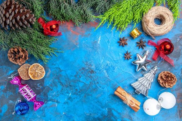 Вид сверху сосновые ветки сосновые шишки соломенная нить рождественские елочные игрушки семена аниса палочки корицы сушеные дольки лимона на сине-красном фоне