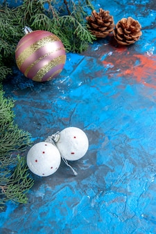 Top view pine tree branches pinecones xmas tree balls on blue-red surface