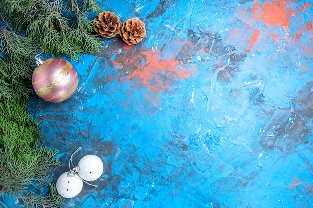 Вид сверху сосновые ветки шишки елочные шары на сине-красной поверхности