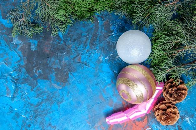 Vista dall'alto rami di pino pigne albero di natale palle nastro su superficie blu-rosso