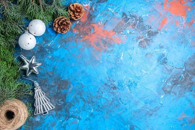 Vista dall'alto rami di pino pigne palle di albero di natale filo di paglia su sfondo blu-rosso