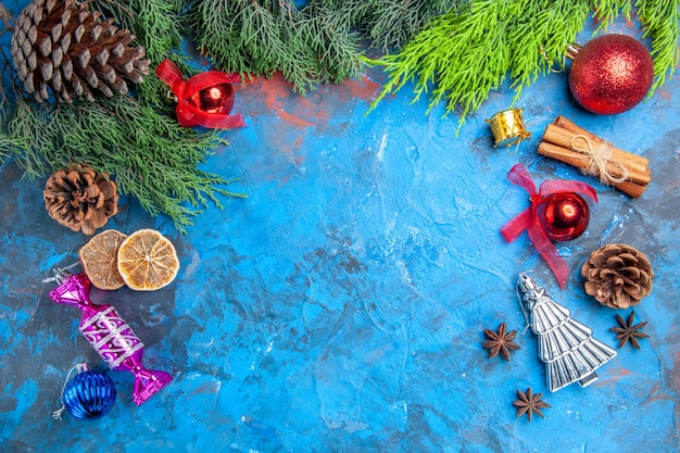 Top view pine tree branches pinecones xmas tree toys anise seeds dried lemon slices on blue-red surface