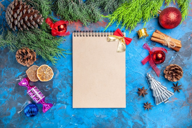 Top view pine tree branches pinecones xmas tree toys anise seeds dried lemon slices a notebook on blue-red background