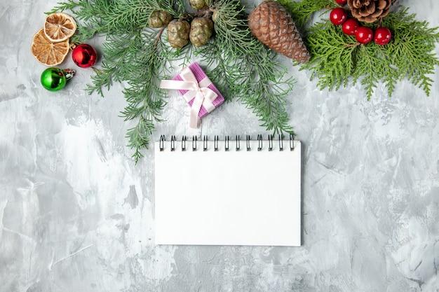 Vista dall'alto rami di pino piccolo regalo albero di natale giocattoli notebook su sfondo grigio
