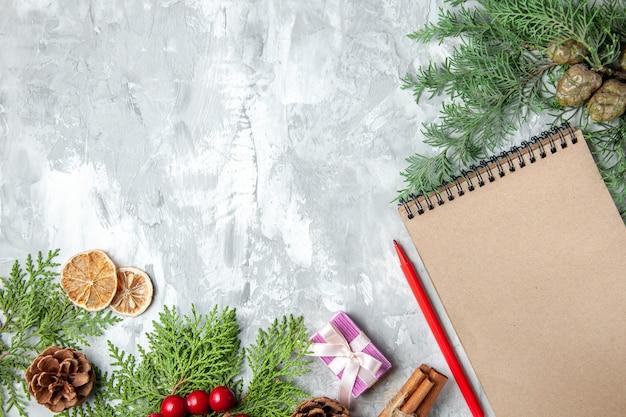 Вид сверху ветки сосны небольшой подарок рождественская елка игрушки тетрадь карандаш сушеные дольки лимона на сером фоне