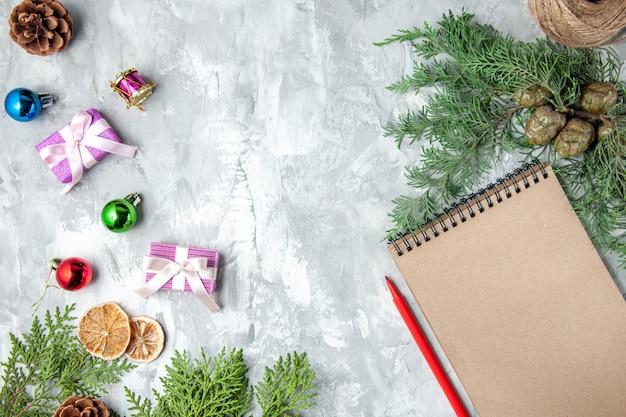 Vista dall'alto rami di pino piccoli regali albero di natale giocattoli matita notebook su superficie grigia