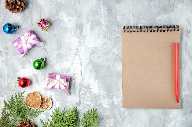 회색 표면에 상위 뷰 소나무 나뭇가지 작은 선물 크리스마스 트리 장난감 노트북 연필