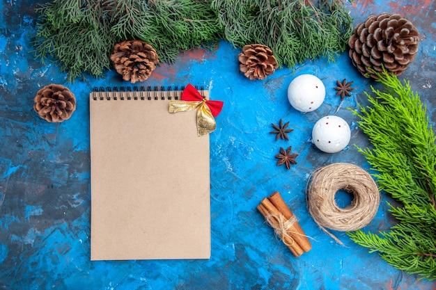 Vista dall'alto rami di pino filo di paglia bastoncini di cannella semi di anice palline di albero di natale bianco un quaderno su sfondo blu-rosso