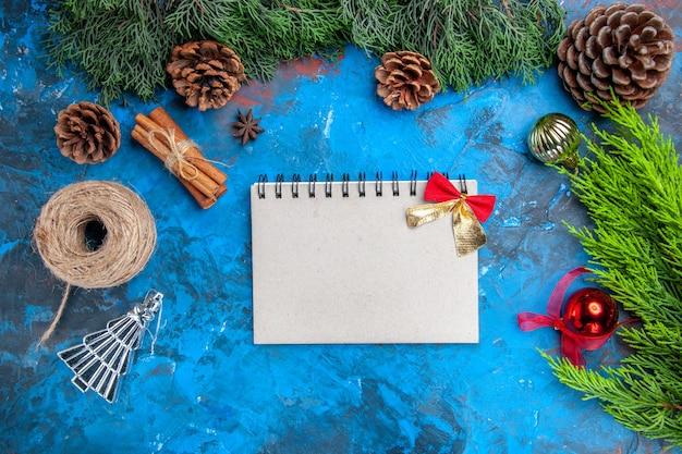 Vista dall'alto rami di pino filo di paglia bastoncini di cannella semi di anice palline di albero di natale un quaderno con fiocco su superficie blu-rossa